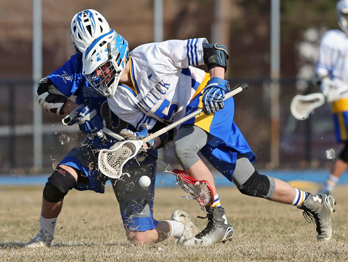 Mattituck's  Dylan Marlborough #15 battles for the face-off with Riverhead's John Ehlers #10. Mattituck was defeated by Riverhead on April 6th 2015 at Mattituck High School. Daniel De Mato