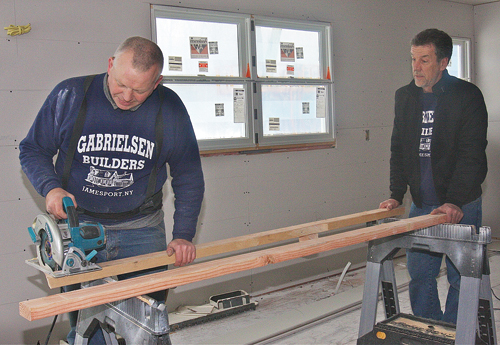 Carpenter Rem Stabas (left) and contractor Tom Gabrielsen working in the kitchen of a Peconic home where they did a complete remodel, gutted all the walls and built two additions. (Credit: Barbaraellen Koch)