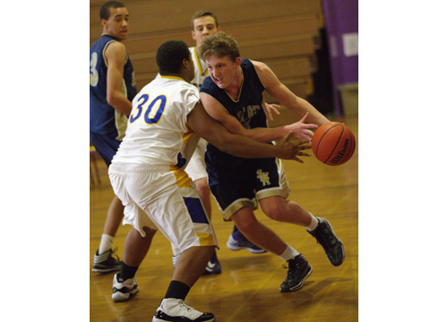 GARRET MEADE PHOTO | Dan Hughes, who scored a game-high 22 points for Shoreham-Wading River, tries to dribble around Greenport's Willie Riggins near the baseline.