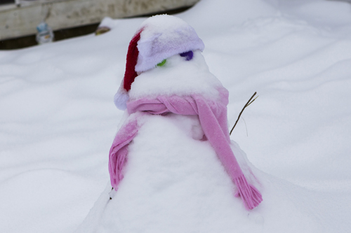 A snowman is covered with more snow in Cutchogue. (Credit: Katharine Schroeder)