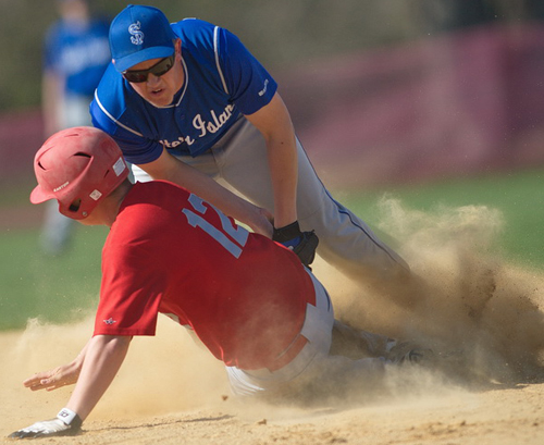 GARRET MEADE PHOTO | Southold's Alex Poliwoda sliding safely under Shelter Island shortstop Hunter Starzee and kicking up a dust cloud.