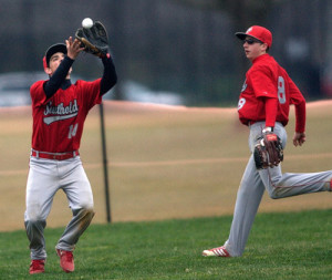 GARRET MEADE PHOTO | Southold's Anthony Esposito catching a fly ball in deep left field, with Shayne Johnson nearby.