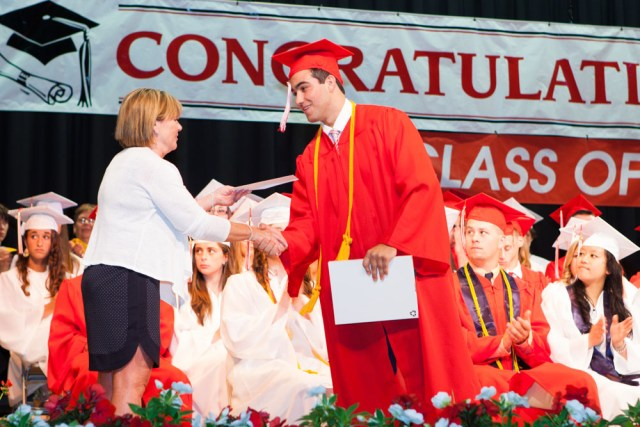 Paulette Ofrias, president of the Board of Education, hands out diplomas.