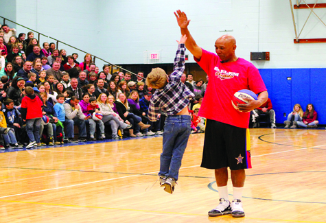 A youngster tries his best to high-five 6-foot, 7-inch Claude Henderson at the Harlem Wizards game at Mattituck High School Thursday night. Proceeds from the sold-out event benefited the Mattituck PTSA.