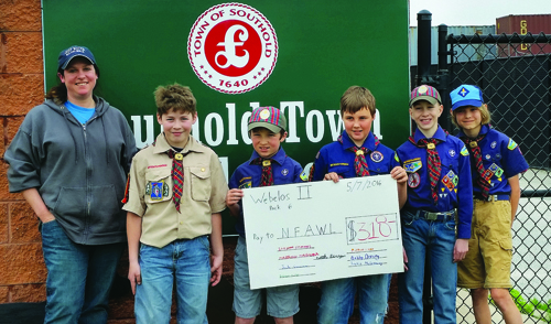 Southold Webelos with their donation 'check' for North Fork Animal Welfare League. From left: kennel manager Gabby Glantzman and scouts Stephen Clements, Jack Goscinski, Noah Berry, Matthew Molnar and Michael Lucak. Not pictured: Justin McGreevy, Brendan Mullen and Bobby Doering. (Credit: courtesy photo)