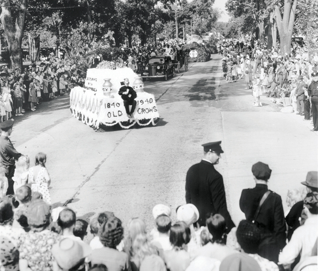 The Tercentenary parade winds its way through a packed downtown Southold in 1940.  At center is the feather-covered float of the 'Old Crows.' (Credit: Southold Historical Society Courtesy Photo)