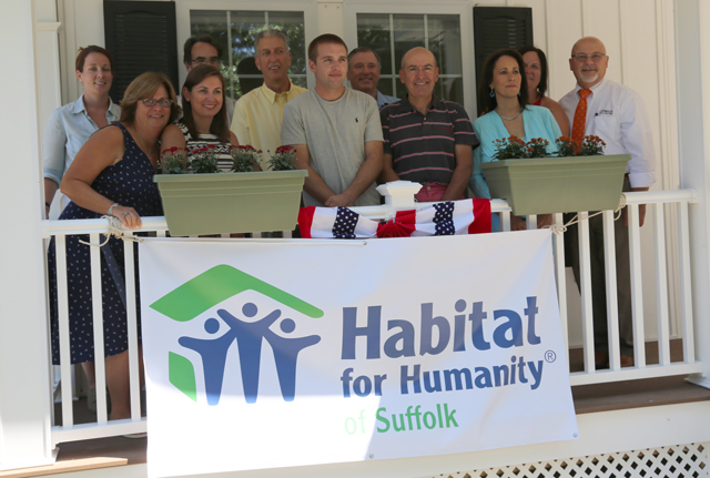 Mr. Bredemeyer, center, stands in front of his new house with the Ruhry family and local business, government and Habitat for Humanity officials Monday.
