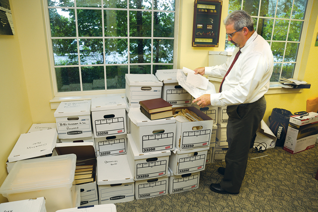 Mattituck-Laurel Library director Jeff Walden looks over the many donated files. (Credit: Paul Squire)