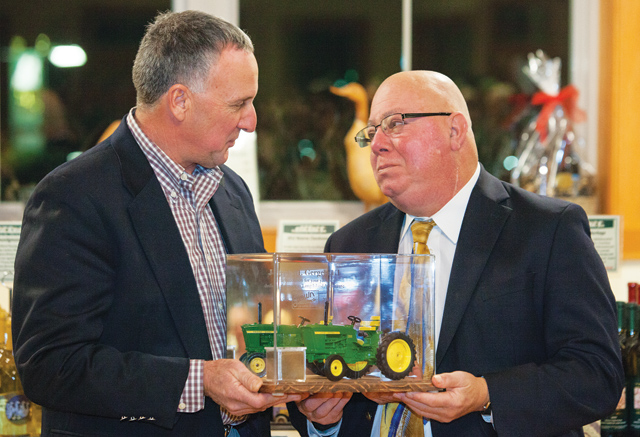 Former Farm Bureau president Mark Zaweski presents Joe Gergela with a miniature tractor as a memento at his retirement party last month. (Credit: Katharine Schroeder, file)