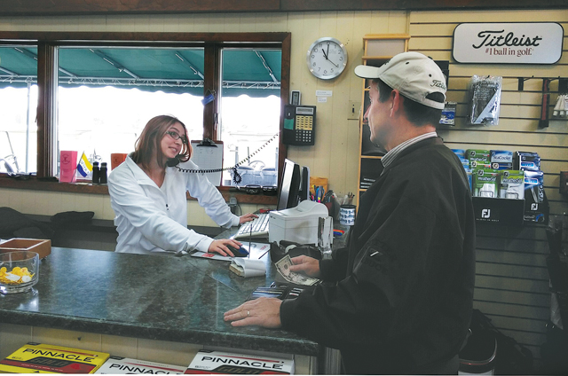 Kaitie Mazzaferro waits on customer Pete Kelly at the Island's End pro shop. (Credit: Jay Dempsey)