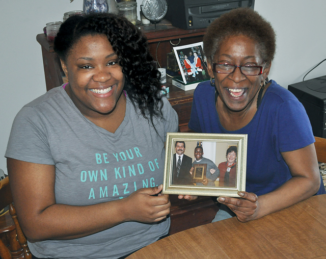 Michael Brown's sister, Karre Brown, and mother, Denise Wilson, hold a picture of the late Greenport resident from his time in high school. Mr. Brown, who had cerebral palsy, was killed in Northampton when his car was struck by a bus in 2010. A scholarship in his name will now benefit a local student with a disability. (Credit: Grant Parpan)