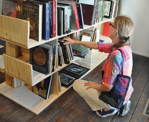 Mary Dowd of Greenport browses art nouveau titles Saturday at a temporary bookstore operating at Art Sites Gallery in Riverhead. Around 400 art books were donated by the family of Southold resident Bob Peters, who died in December. (Credit: Rachel Young)