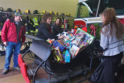 Former Cutchogue Fire Department chief and toy coordinator Tom Shalvey looks on as Capital One Bank branch manager Diane Biondi (far left), assistant manager Anjiolo Gonazlez and relationship banker Trinity Fleischman load a sleigh with $500 worth of toys Friday morning. The gifts will be donated to local charities. (Credit: Barbaraellen Koch)