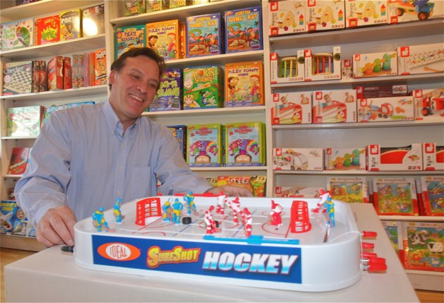 Love Lane Toys store owner Alex Dank demonstrates how the 'retro' toy Sure Shot Hockey works Monday afternoon. (Credit: Barbaraellen Koch)