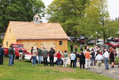 Members of the Cutchogue-New Suffolk Historical Council and the community gather to watch the dedication of the new village garage on Cutchogue Village Green Sunday. The garage was built by the historical council to house 20th century historical memorabilia, including a Model T Ford donated by Parker Wickham, who died several weeks ago.