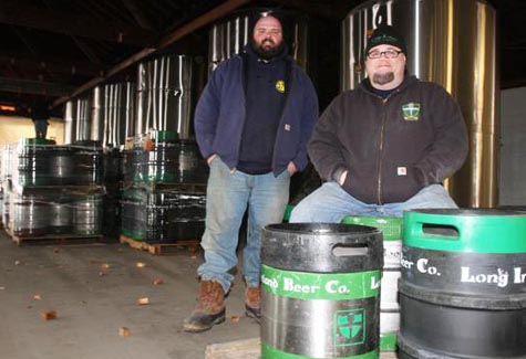 BARBARAELLEN KOCH PHOTO | Long Ireland Beer Company owners Dan Burke (left) and Greg Martin pose with kegs and five fermentation tanks in their Riverhead brewery.