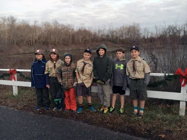 The Cub Scouts pose in front of the fence. (Courtesy photo)