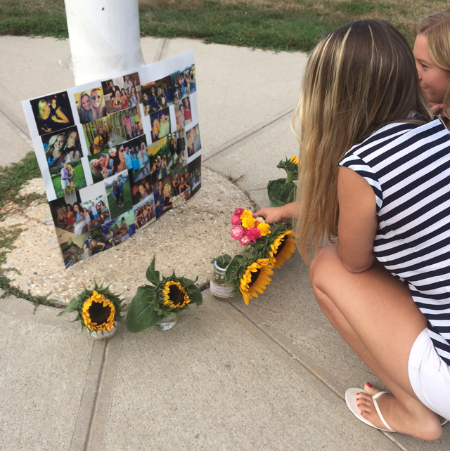 Rebecca Jensen and Megan Drobny, both of Greenport, place flowers at a memorial for Kaitlyn Doorhy outside Mattituck-Cutchogue high School Saturday evening. (Credit: Jessica DiNapoli)