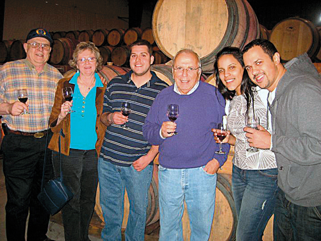 """Pindar Vineyards proprietor """"Dr. Dan"""" Damianos (in purple sweater) hosts a barrel tasting and behind-the-scenes tour for Pindar Wine Club members. (Credit: Courtesy photo)"""