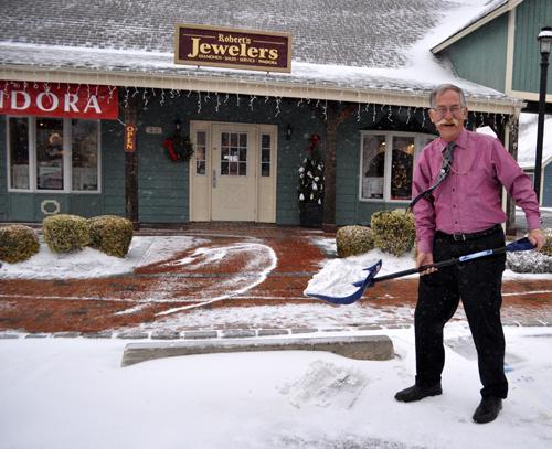 Robert's Jewelers owner Robert Scott, snow shovel in hand, at his Southold store Thursday morning.