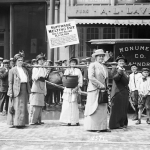 """A group of suffragists in Boston carry a """"Suffrage Melting Pot"""" in which gold and silver and old and new articles of any sort that were put in the melting pot were converted into cash by the US mint in 1914.BETTMANN/BETTMANN ARCHIVE"""
