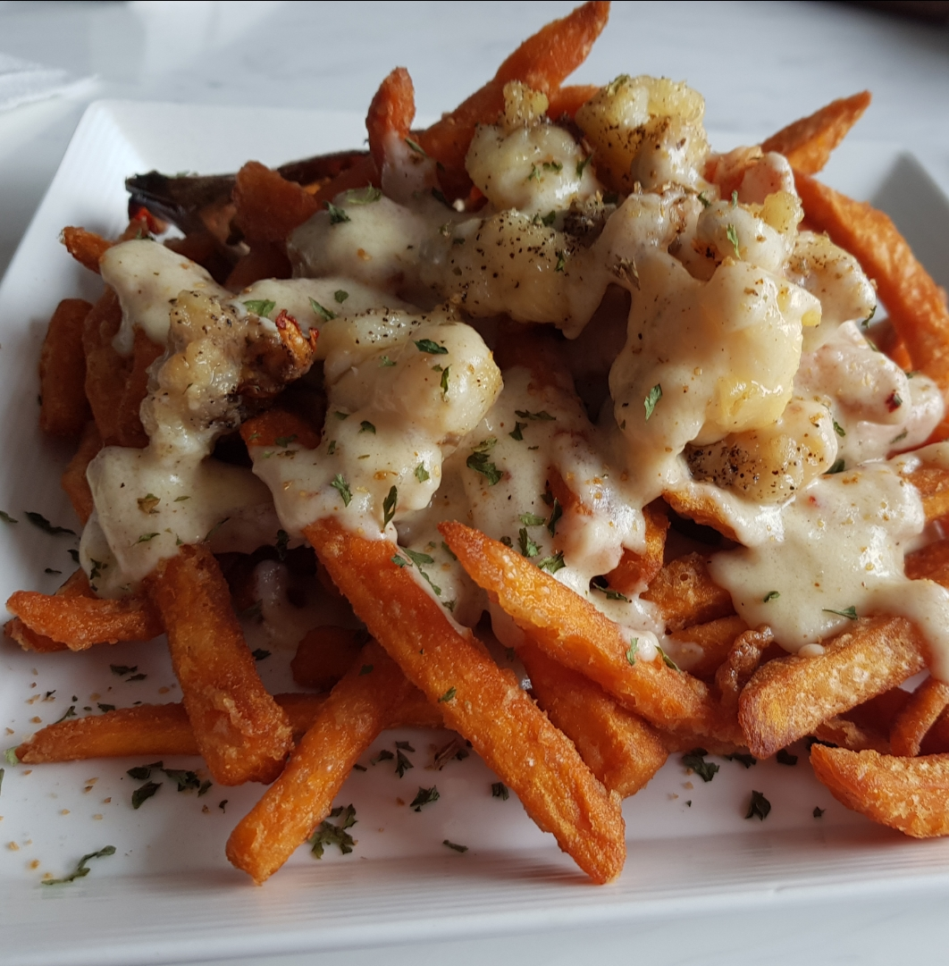 Loaded Lobster Fries (Crispy seasoned sweet potato fries with chunks of lobster finished with a creamy chive cheese sauce ($1790JMD+tx+10% serv. charge)