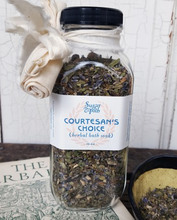 Sugar and Pith Courtesan's Choice herbal soak, square Victorian bottle full of herbs on a book with a bowl full fo herbs next to it