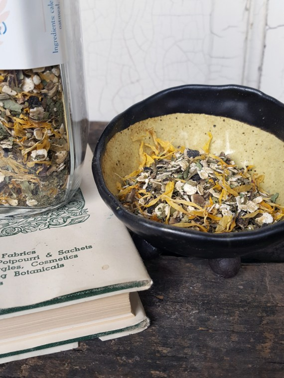 Sugar and Pith Maiden's Blush herbal soak, part of a jar of bath herbs sitting on a book with a bowl of herbs next to it