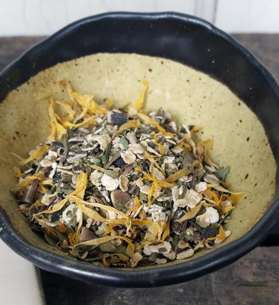 Sugar and Pith Maiden's Blush herbal soak, bath herbs in a rustic ceramic bowl