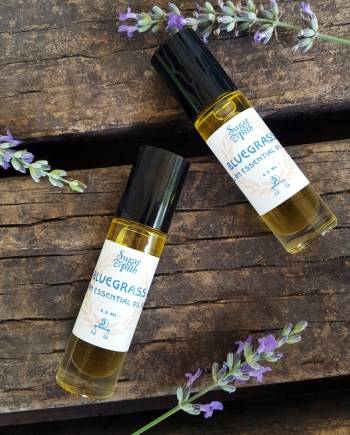 Sugar and Pith, Roll On Veranda, two roll on bottles of essential oils laying on a rustic wood surface askew with lavender spikes set around them