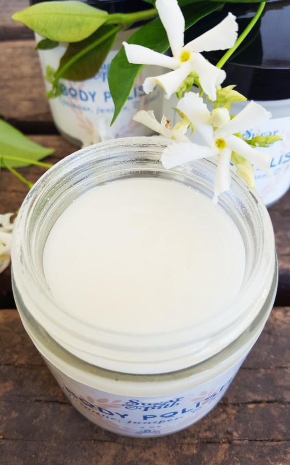 Sugar and Pith, Jasmine Juniper and Lime Body Polish, tight shot of jar of body polish from above with a jasmine flower set on the rim.