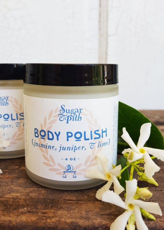 Sugar and Pith, Jasmine Juniper and Lime Body Polish, two jars of body polish one in the foreground and one slightly behind it to the left and a few jasmine flowers set just in front of them.