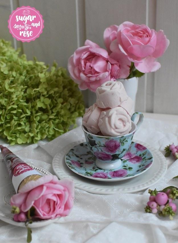 Roseneis in Form von kleinen Rosenblüten aufgetürmt in einer hellblauen Mokkatasse mit Untertasse, beides mit Rosenmotiven, dahinter eine weiße Vase mit zwei rosa Rosenblüten, davor ein Waffelhörnchen mit einer Rosenblüte