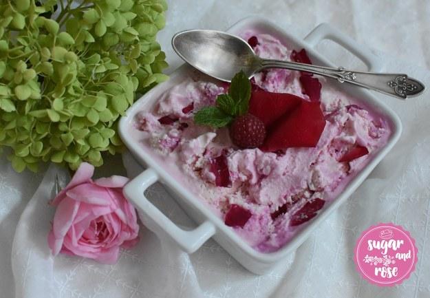 Quadratische weiße Keramischale mit zwei Henkeln, gefüllt mit rosa-weiß marmoriertem Roseneis mit roten Rosenblüten, dekoriert mit einer Himbeere, darüber ein antiker Silberteelöffel, daneben eine rosa Rose und eine hellgrüne Hortensienblüte