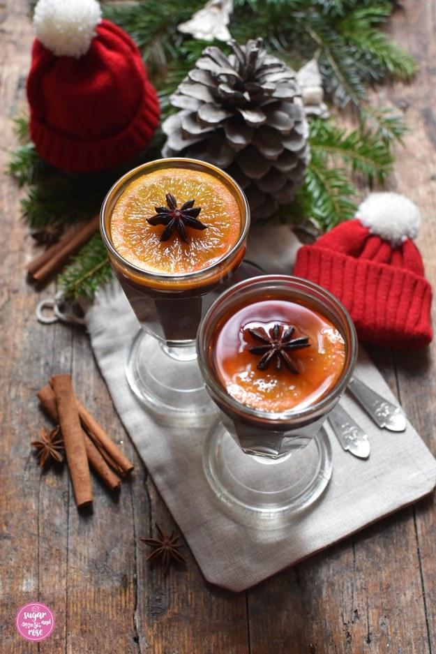 Zwei alte Teegläser aus Pressglas mit Stiel, gefüllt mit Punsch, Orangenscheibe und Sternanis, daneben auf einem rustikalen Brett Tannenzweige, ein Zapfen, zwei kleine rote Wollmützen mit weißer Quaste, davor Zimtstangen