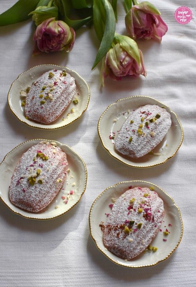 Vier Madeleines auf kleinen Vintage-Tellern mit Tulpenstrauß