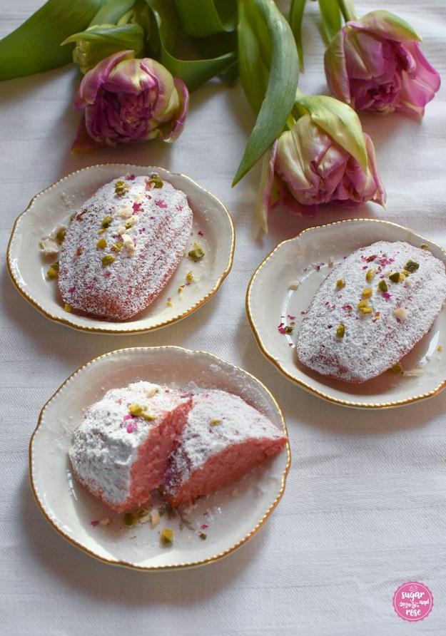 ´Madeleines auf kleinen Vintage-Tellern mit Tulpenstrauß, ein Madeleine angeschnitten