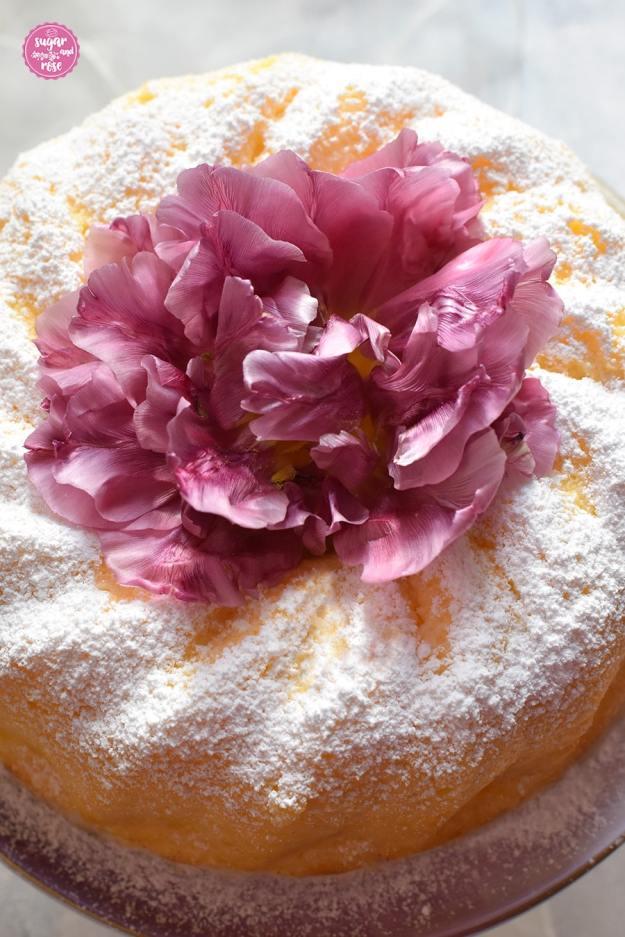 Detailansicht des Topfengugelhupfs, von oben fotografiert, mit einer dicken Puderzuckerschicht und einer lila Tulpenblüte in der Gugelhupfmitte als Dekoration