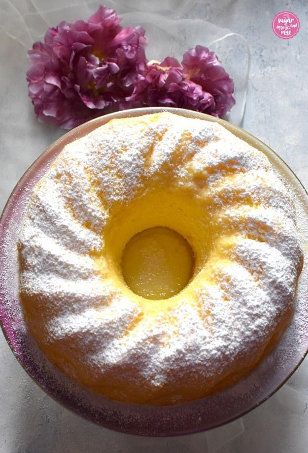 Sonnig gelber Topfengugehlhupf auf rosa Tortenständer, daneben lila Tulpen. Der Gugelhupf leuchtet von der Mitte heraus sonnengelb und wirkt ursaftig.