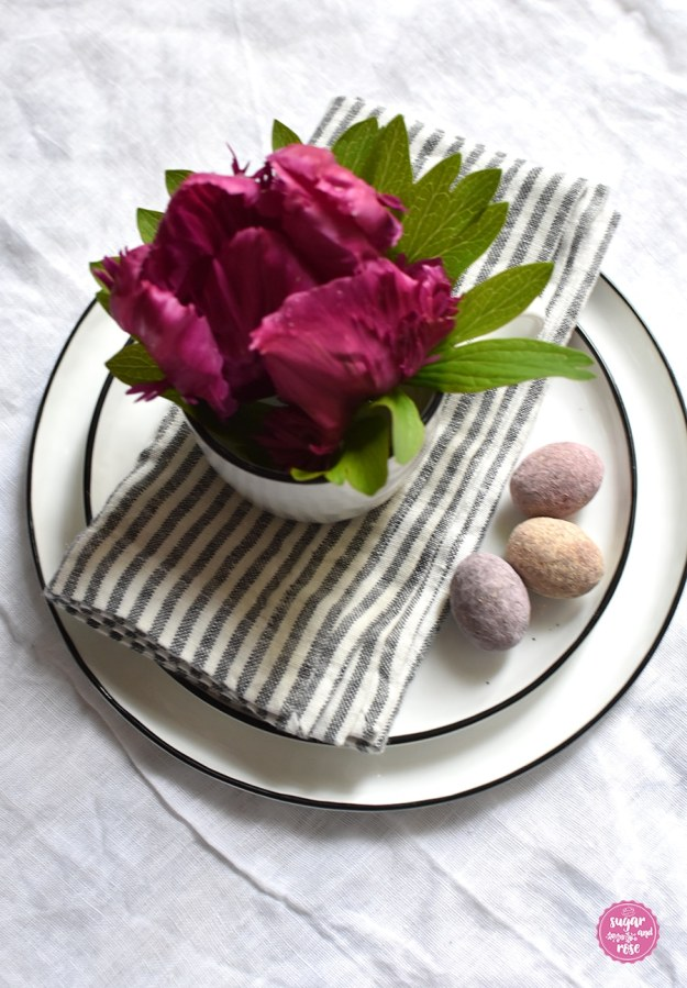 Teller und Schale mit Serviette, drei Lindt Fruchteiern und einer Schale mit einer weinroten gefierderten Tulpe