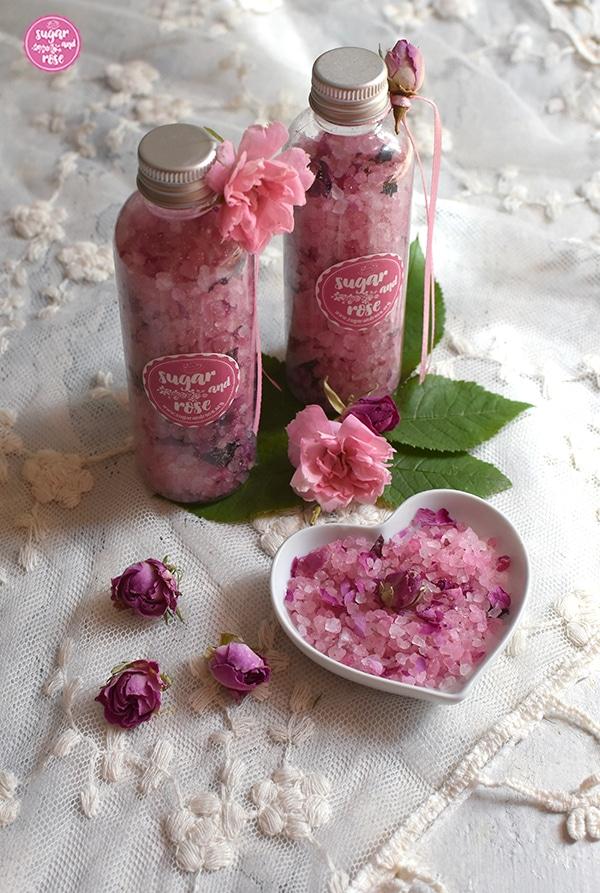 Rosa Rosenbadesalz mit getrockneten rosa Rosenblüten in einer kleinen herzförmigen Keramikschale und abgefüllt in zwei durchsichtigen Fläschchen, dekoriert mit rosa Bändchen, einem kleinen rosa Röschen und rosa Etiketten sugar&rose