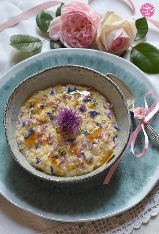 Sommer-Porridge mit bunten Wiesenblumen in einer einer grauen Schale mit Silberlöffel, dahinter zwei rosa Rosen mit einem rosa getupften Bändchen; die Schale steht auf einem türkis marmorierten Teller. Das Porridge ist garniert mit blauen Kornblumenblüten, rotem Hornklee und gelbem Löwenzahn, darüber etwas Löwenzahnsirup geträufelt