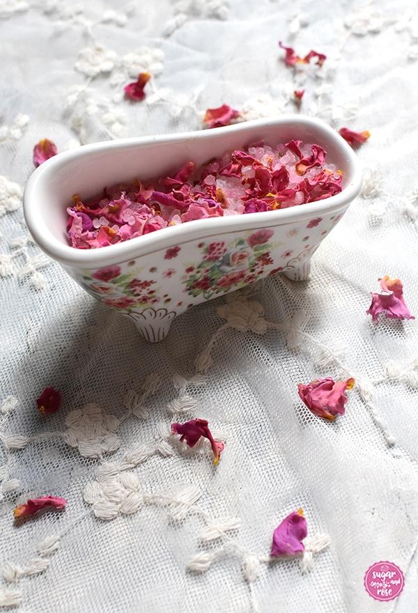 Mini-Dekor-Badewanne mit Füßchen und Rosendekor außen, gefüllt mit Rosenbadesalz und pinkrosa getrockneten Rosenblüten, stehend auf einem Vintage-Gazetuch mit gestickten Blüten
