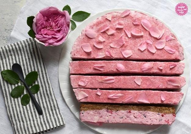 Geeistes Beerentörtchen mit Schoko-Mürbteigboden und einer fluffigen rosa Himbeer-Heidelbeer-Cheescakeschicht, zur Hälfte in längliche Stücke geschnitten, als Deko eine weiß-grau-gestreifte Stoffserviette und eine kleine Schale mit einer rosa Rosenblüte