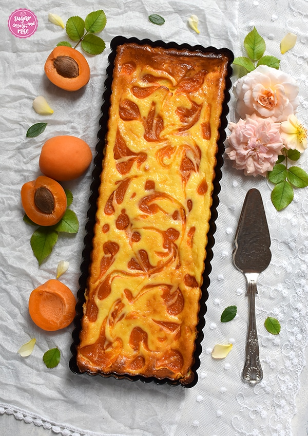 Marillen-Ricotta-Tarte in länglicher Tarteform auf weißem Spitzenschal mit aufgeschnittenen Marillen, apricotfarbenen Rosenköpfen und einem silbernen Tortenheber