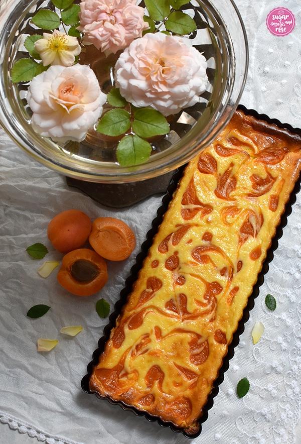 Marillen-Tarte in länglicher Tarteform auf weißem Spitzenschale, daneben eine Jugendstilschale mit Glaseinsatz und schwimmenden apricotfarbenen Rosenköpfen