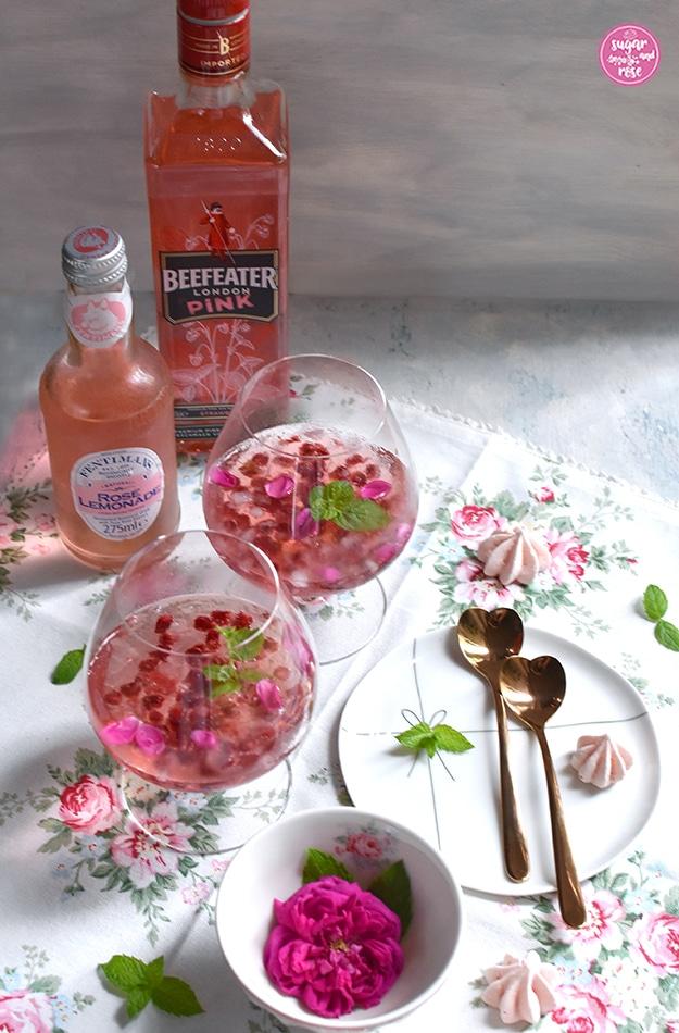 Rosé-Gin-Cocktail mit Granatapfelkernen in zwei Cognac-Schwenkern, daneben ein zarter weißer Porzellanteller mit zwei rosegoldfarbenen, herzförmigen Metalllöffelchen, eine Schale mit einer pinkfarbenen Rose und zartrosa Baisertuffs auf einer weißen Leinenserviette mit zartrosa Rosenmotiven. Daneben stehen eine Flasche Beefeater London Pink Gin und ein Fläschen Fentimans Rose Lemonade