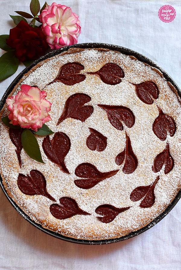 Herzerl-Ricotta-Tarte mit Zwetschkenmus in einer runden Tarteform, dekoriert mit rotrandigen Rosen