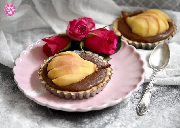 Birnen-Schoko-Tartelette auf einem rosa Desserteller, dazu drei pinkfarbene Rosenköpfe, daneben ein alter silberner Dessertlöffel