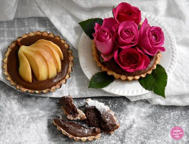 Ein Birnen-Schoko-Tartelette, daneben eine Tartelette auf weißem Vintage-Dessertteller, dekoriert mit fünf pinkfarbenen Rosenköpfen, davor ein Stück von einem Schokotartelette
